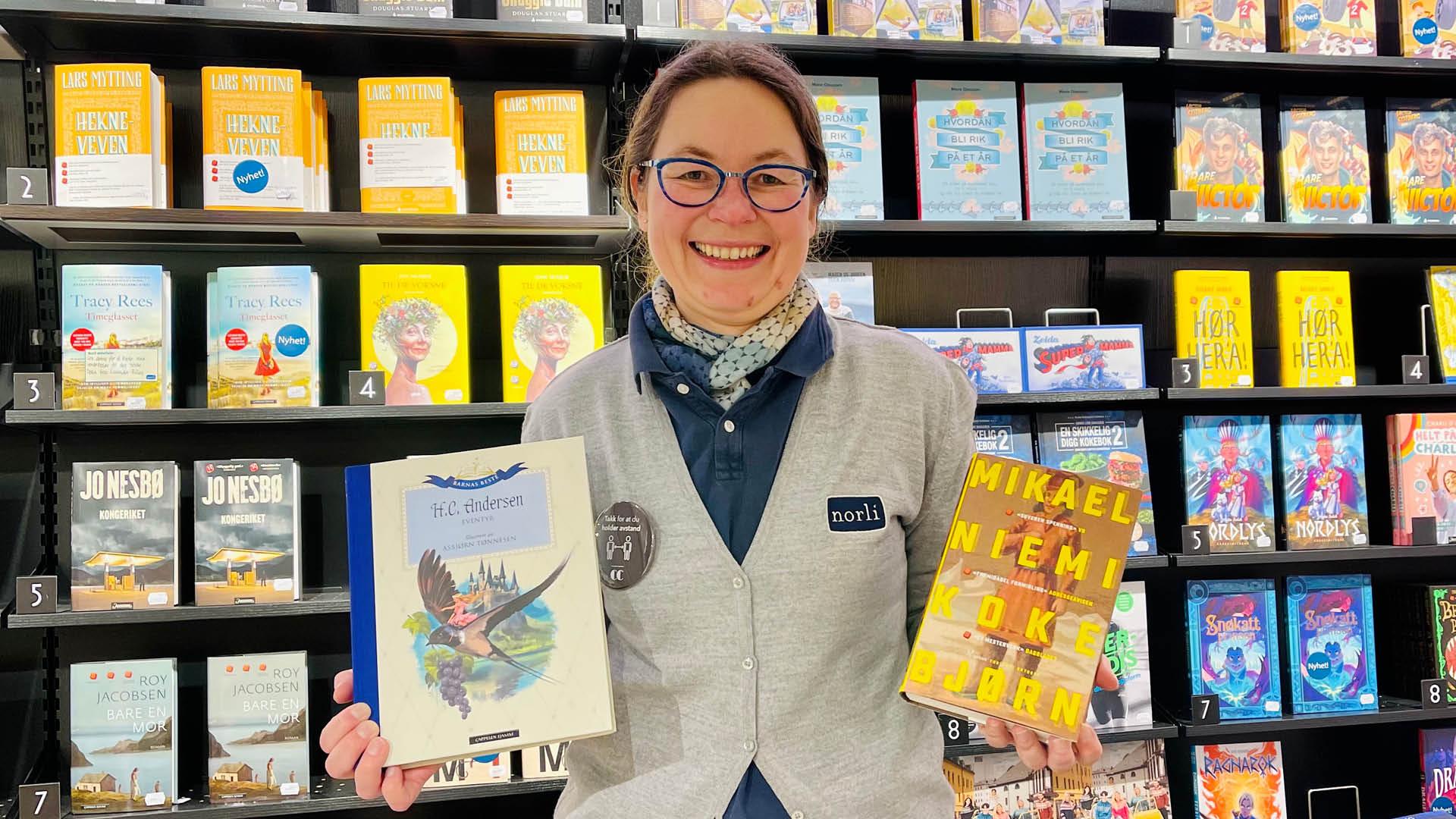 Dame viser bøker fra Mammut-salget på CC Gjøvik