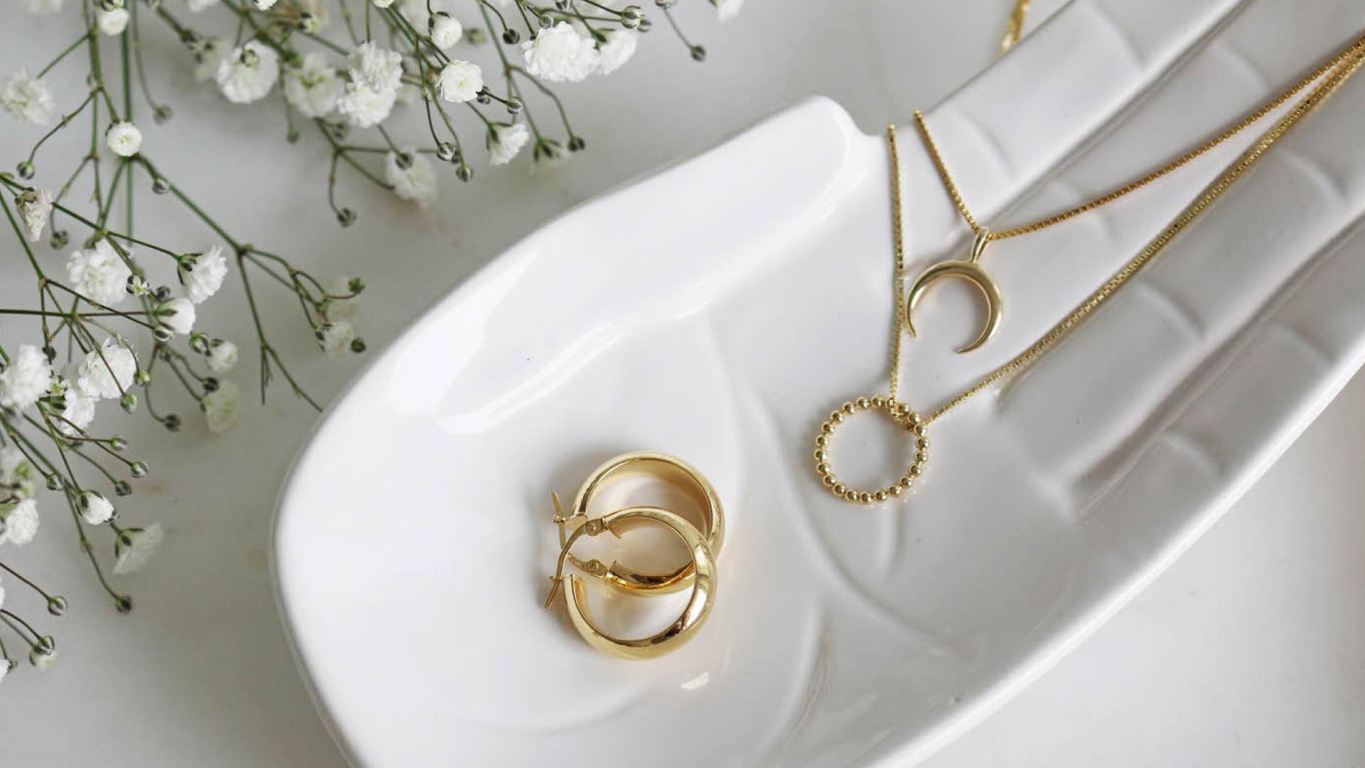 Bilde av gullsmykker i en skål formet som en hånd