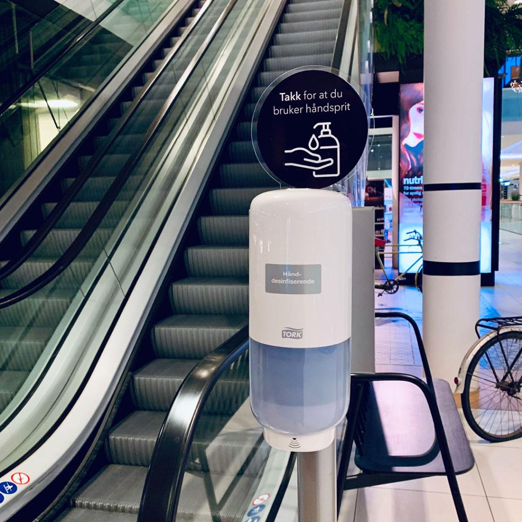 Bilde av håndspritautomat plassert ved rulletrapp