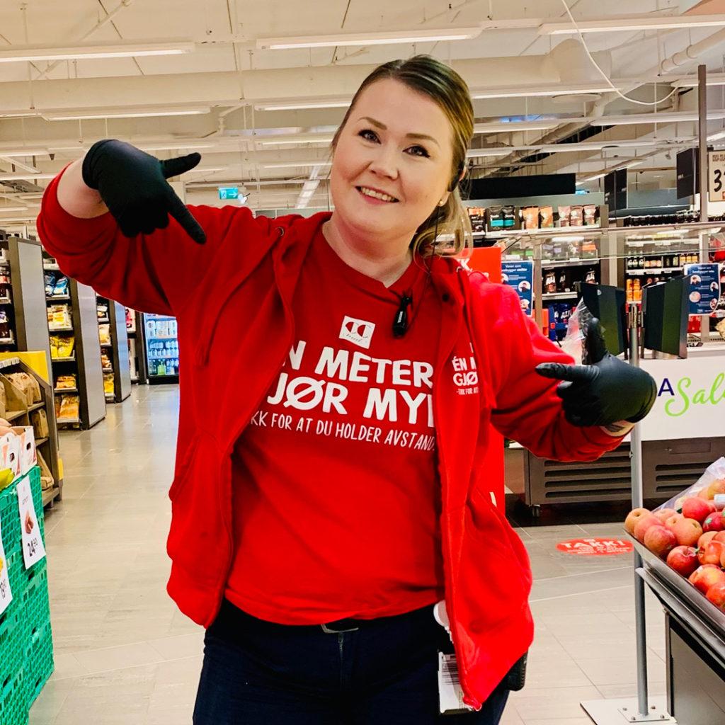 Bilde av CC Mat ansatt som peker på genser med budskap om å holde avstand