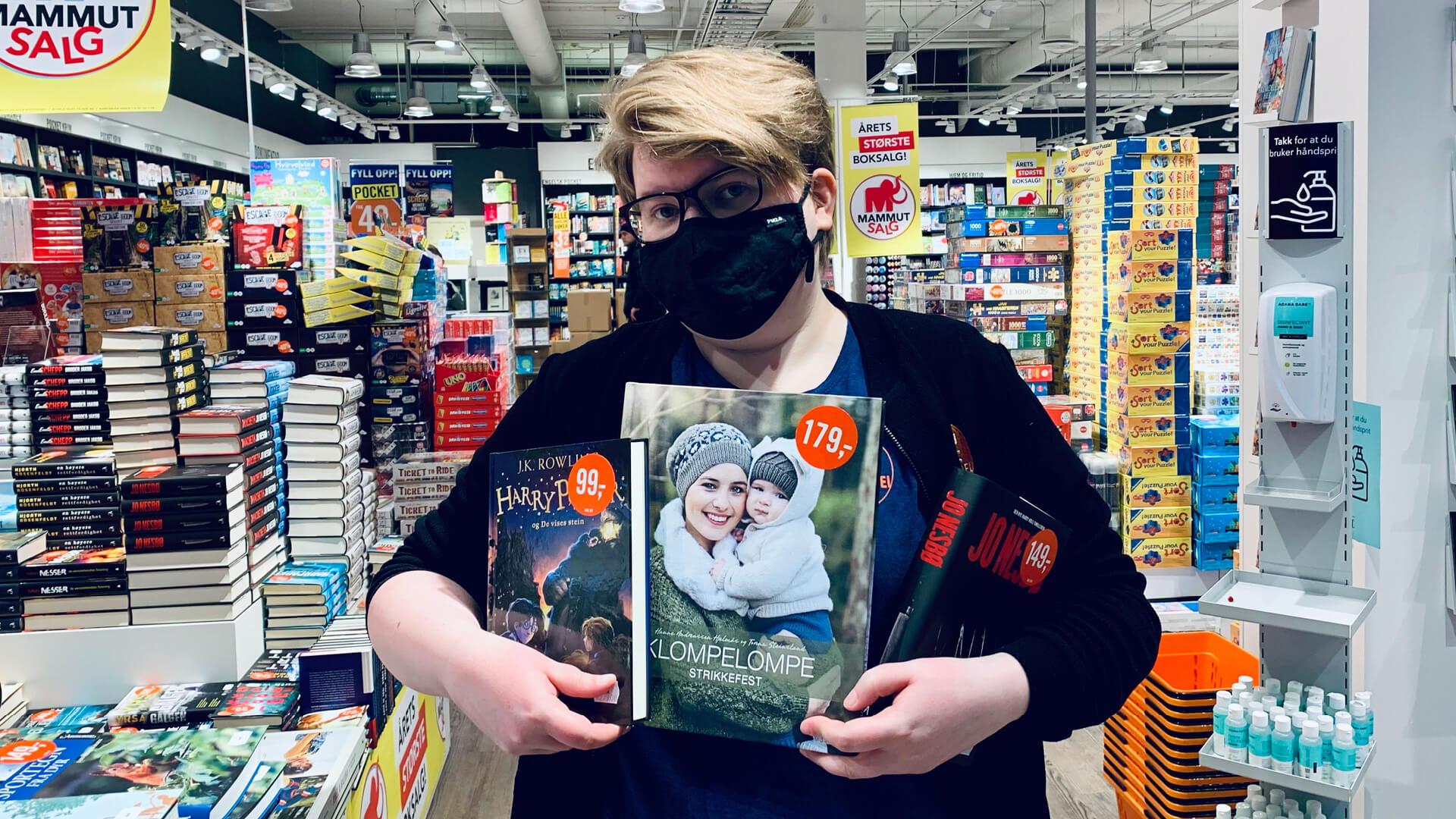 Bilde av ARK ansatt som holder tre bokanbefalinger