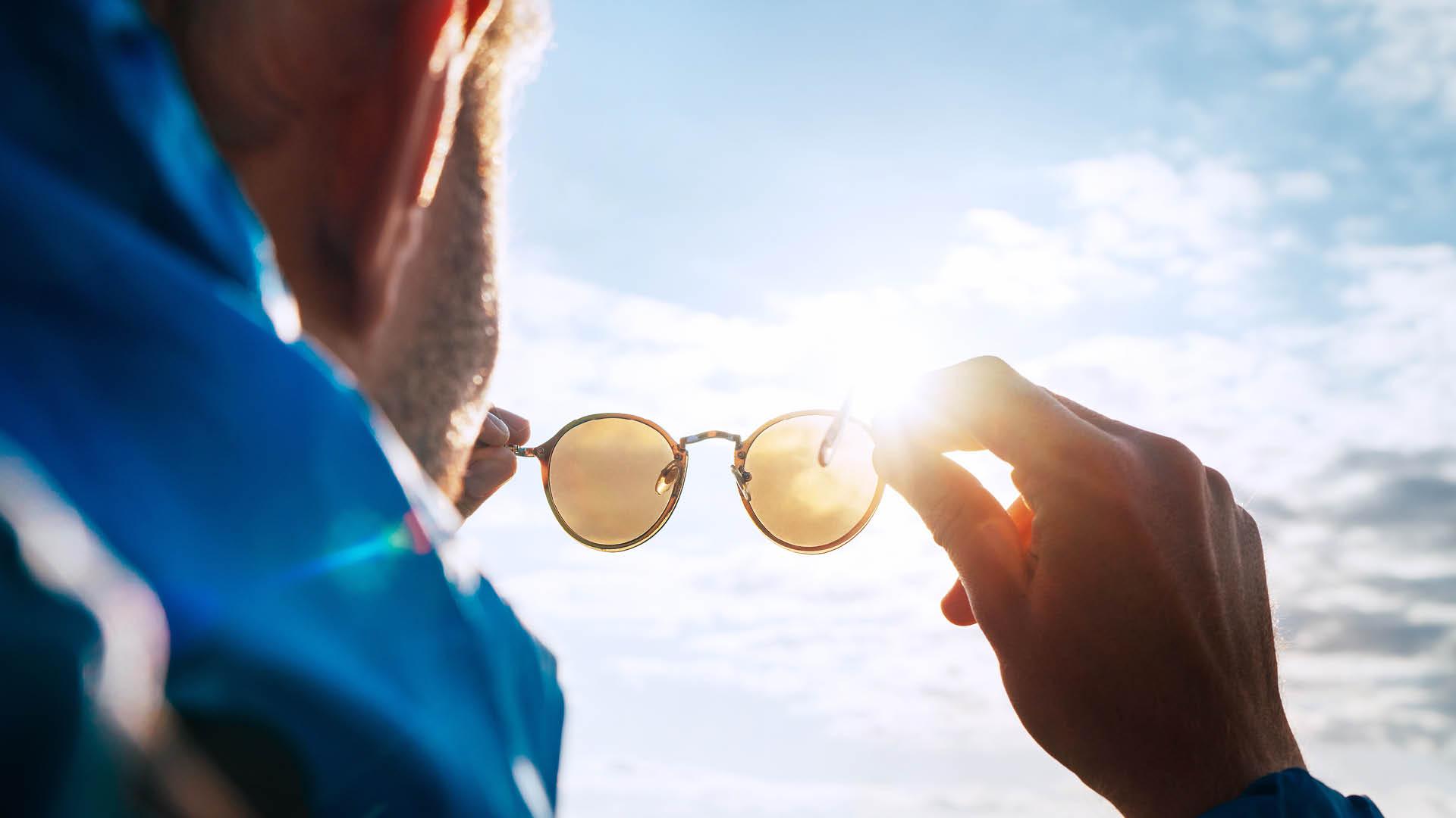 Mann med solbriller i hendene mot en solfylt himmel.