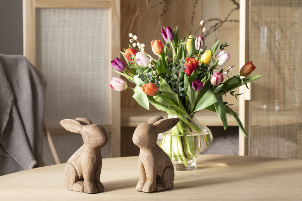 Bord med påskeharer i tre og blomster fra Mester Grønn.
